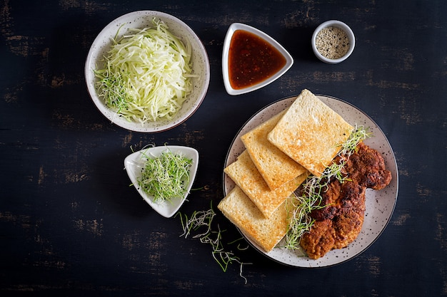 Food trend japanese sandwich with breaded pork chop, cabbage and tonkatsu sauce.