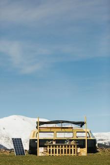 雪が積もった山々のある緑の野原にあるフードトラックバン