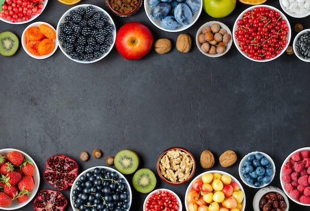 抗酸化物質を多く含む食品:ベリー、ナッツ、フルーツ。黒のコンクリートの背景。スペースをコピーします。