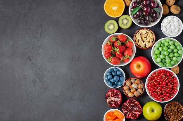抗酸化物質を多く含む食品:ベリー、ナッツ、果物。黒のコンクリートの背景。スペースをコピーします。