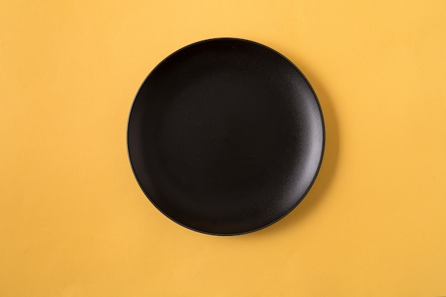 Food with empty black plate, over yellow, flat lay.