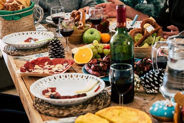 ダイニングテーブルにワインボトルとワイングラスを置いた料理。スライスした肉、テーブルに置いたパンと新鮮な果物。ボトルとグラスにワインを入れた作りたての調理済み食品と収穫された果物。