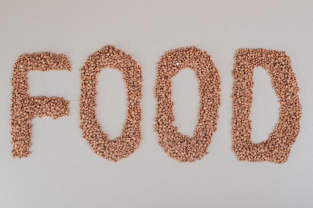 Scrittura di cibo con fagioli marroni su cemento.