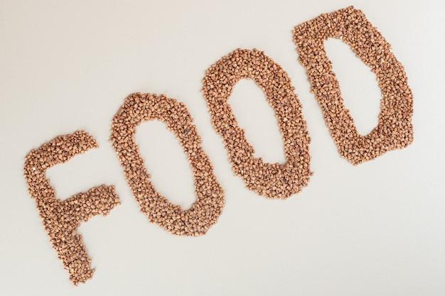 Scrittura di cibo con lenticchie verdi su fondo bianco.