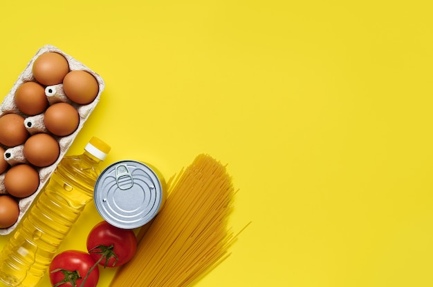 Food on yellow background, chicken eggs, sunflower oil, tomatoes, pasta, canned food, top view, flatlay