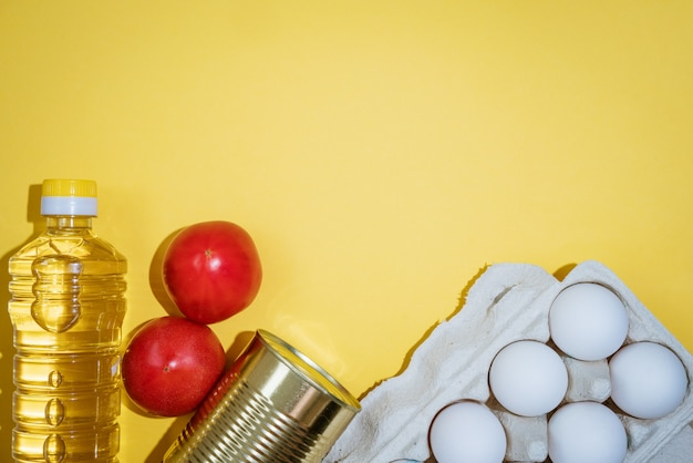 Food on a yellow background, vegetables eggs and oil