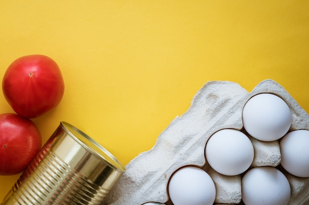 Food on yellow background, vegetables eggs and oil