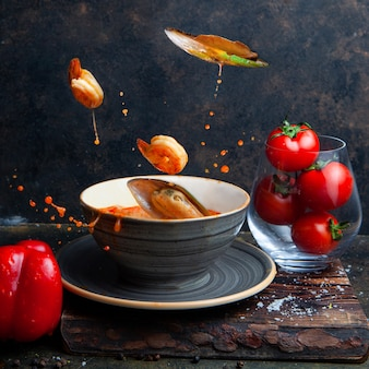 Foods flying in the air with tomatoes on black textured background side view