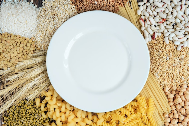 Foods high in carbohydrate on wooden background. loaf, pasta, pearl barley and oats.