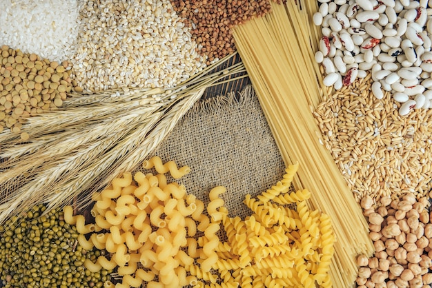 Продукты с высоким содержанием углеводов на деревянных фоне. булка, макароны, крупа перловая и овес.