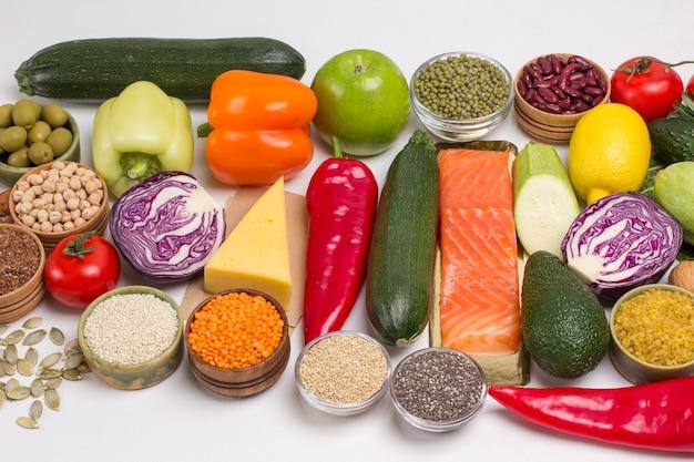 脂肪酸、タンパク質、サーモン、チーズ、野菜、ナッツ、種子を多く含む食品。白色の背景
