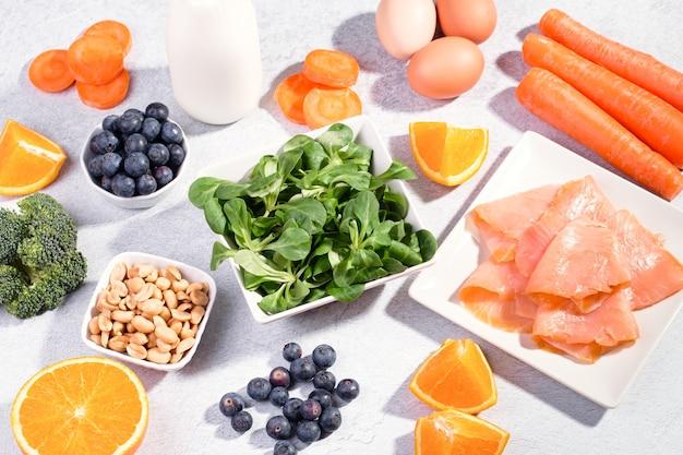 目を健康に保つのに役立つ食品、視力を維持するための製品。コピースペース、コンクリートの背景に目の健康のための食品の品揃え、フラットレイ、上面図、誰もいない黒板
