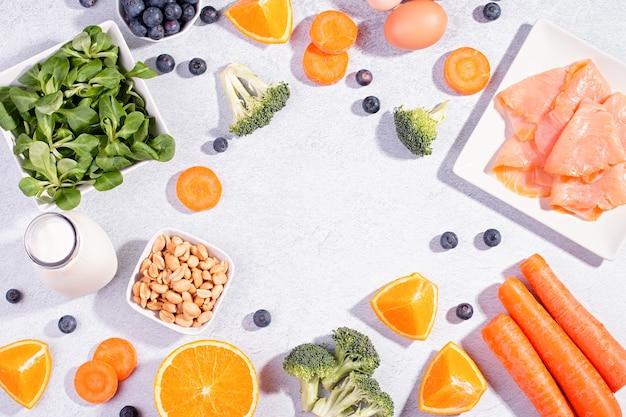 目を健康に保つのに役立つ食品、視力を維持するための製品、目のためのビタミン。コピースペース、コンクリートの背景に目の健康のための食品の品揃え、フラットレイ、上面図のブラックボード
