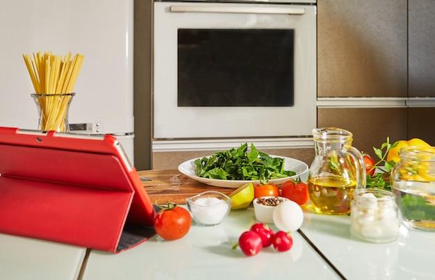 집에서 부엌에서 건강식을 요리하는 동안 터치 태블릿을 사용하여 디지털 레시피 가상 온라인 마스터 클래스 튜토리얼에서 요리 할 음식.
