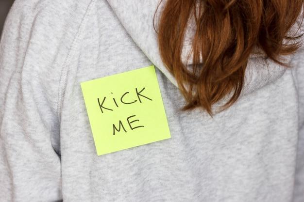 Fool'day jok. sticker 'kick me' on teenager girl's back.