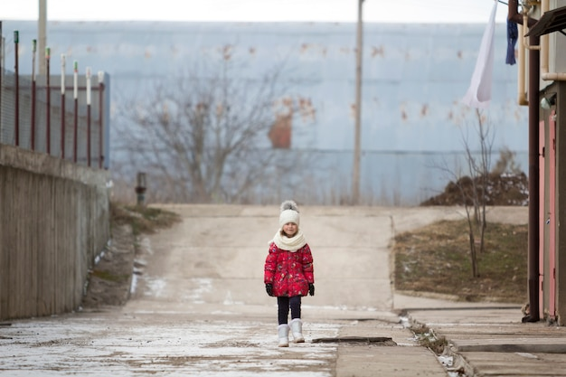 Fool-length portrait of cute little young funny pretty child girl in nice warm winter clothing walking confidently alone