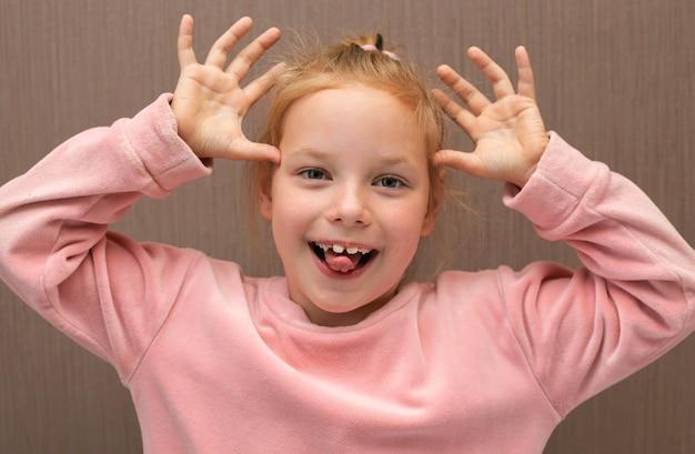 Дурачусь. маленькая девочка высунув язык и морщась