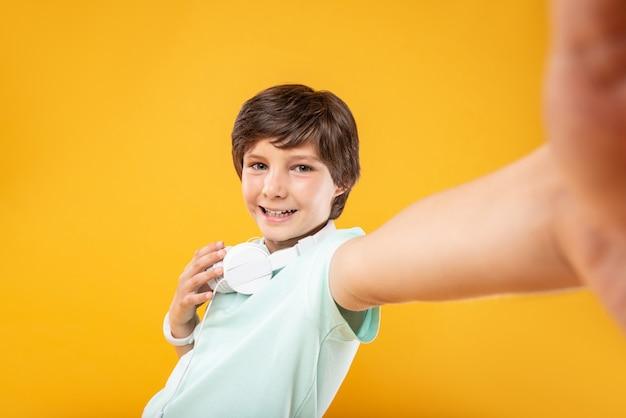 浮気。ヘッドホンをつけて自分撮りをしているスリムな男の子に満足