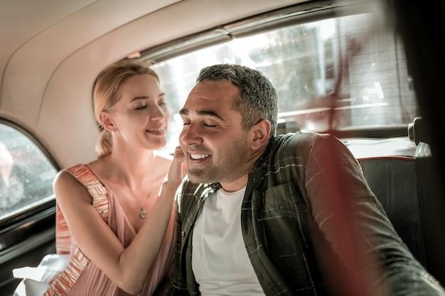 장난. 차 뒷좌석에 남편과 함께 앉아 목을 간지럽히는 웃는 여자.