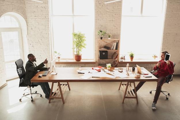 Дурачится перед своим боссом. кавказский рабочий, менеджер пытается работать в офисе.