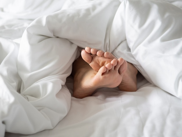 Foot in blanket on cozy bed in morning