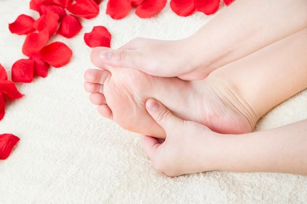 フットケア。美しい女性の脚とバラの花びら