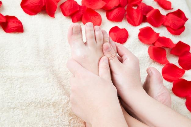 Foot care. beautiful female legs and rose petals