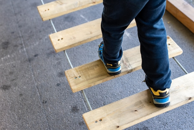 Foot of child doing balances on wooden boards in an urban adventure park.