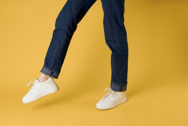 발 제스처 흰색 운동화 패션 청바지 거리 스타일 노란색 배경