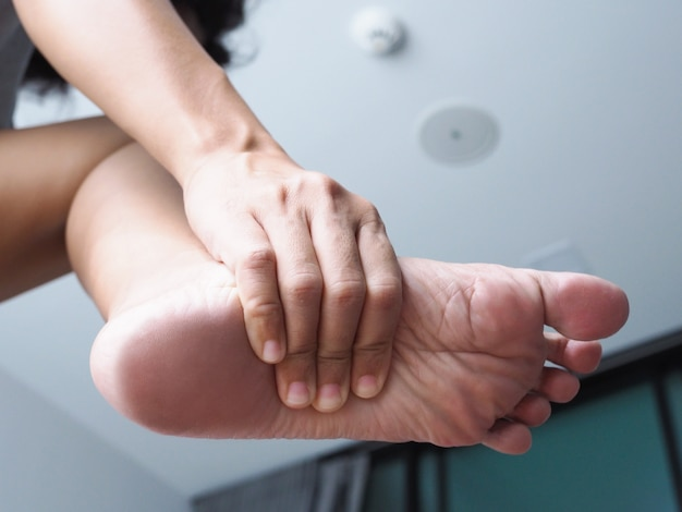 Foot injury use hand massage on feet to relax muscle from heel pain