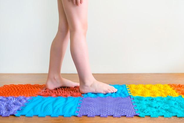발 마사지. 어린이 발은 정형 외과 매트를 걷습니다. 평발 및 다리 질환의 치료 및 예방
