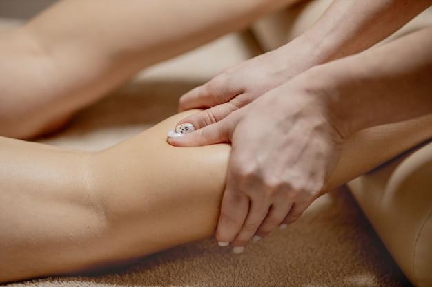 마사지 팔러에서 발 마사지-여성의 손이 여성의 발을 마사지-아름다움과 건강.