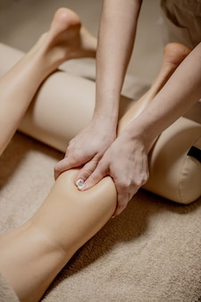 マッサージパーラーでの足裏マッサージ-女性の手が女性の足をマッサージします-美しさと健康。