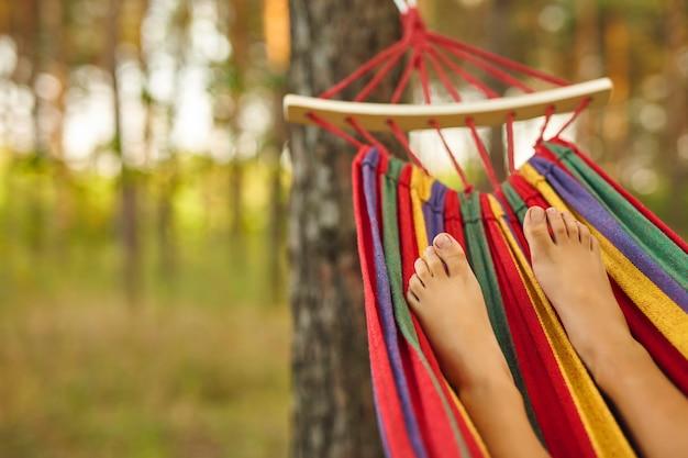 ハンモックに横になって晴れた日にリラックスする子供の足。はだし。ライフスタイルのコンセプト。