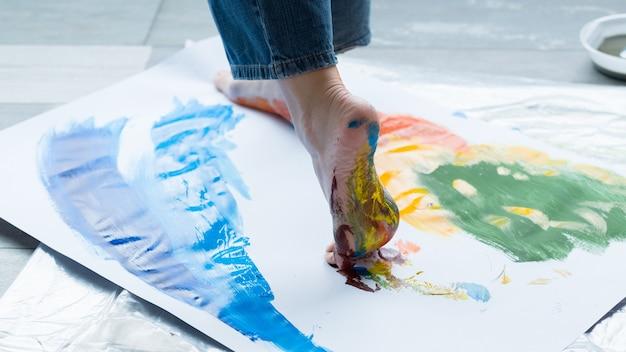 足の塗装技法。カラフルな抽象的なアートワークを作成し、紙の上を歩いているアーティストのトリミングされたショット。