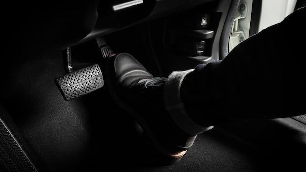 운전할 자동차의 발 페달을 밟습니다. 자동차의 가속기와 브레이크 페달. 가속기를 누르고 자동차의 페달을 끊음으로써 자동차를 운전하는 운전자. 차량 내부. 컨트롤 페달. 확대.