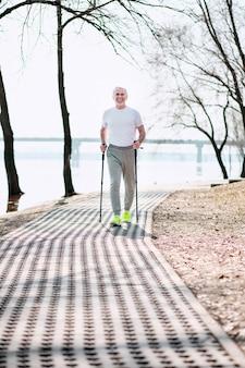 Состязание в беге. энергичный зрелый мужчина занимается спортивной ходьбой в парке, наслаждаясь погодой