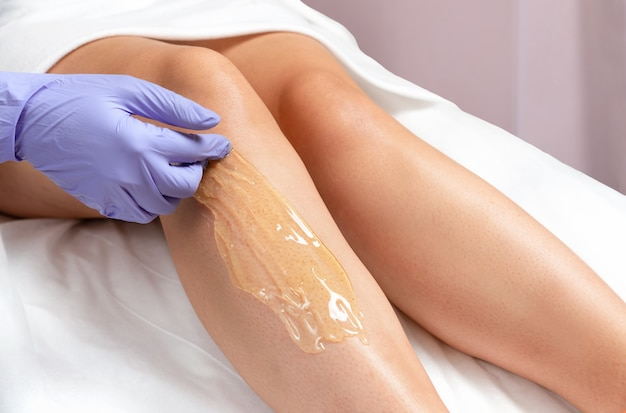 Foot sugaring procedure in a beauty salon. a gloved master applies sugar paste on a woman's leg for depilation.