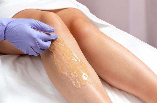 Процедура шугаринга ног в салоне красоты. мастер в перчатках наносит сахарную пасту на ногу женщины для депиляции.
