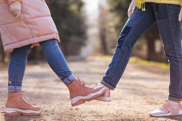 フットタップ。コロナウイルスの蔓延を防ぐための新しい小説の挨拶。 2人の女性の友人が公園で会います。抱擁や握手で挨拶する代わりに、彼らは代わりに一緒に足に触れます。