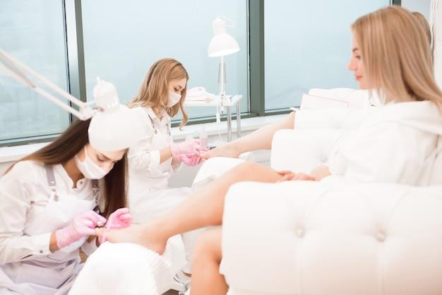 Уход за ногами для двоих подруг или сестер в спа салоне. художник по маникюру в салоне красоты, делая педикюр для ног клиентов.