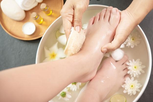 トリートメント前のスパでの足洗い。女性の足と手のスパのためのスパトリートメントと製品。
