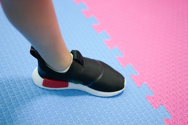 체육관 바닥에 덜 검은 신발 끈에 발 착용 스포츠 운동화