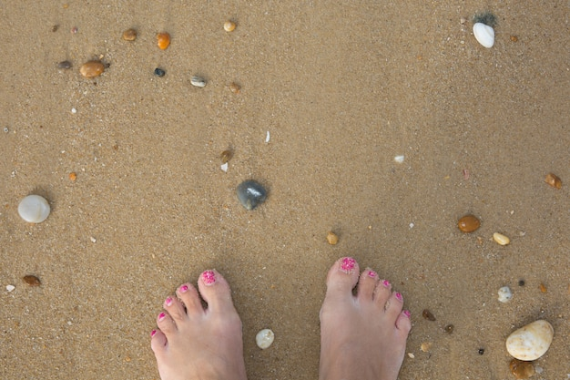 Foot of woman and shells and peebles on the beach.