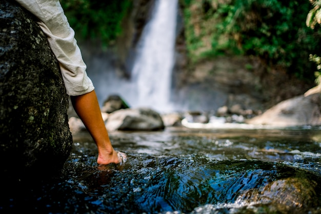 Foot of a woman in the water of a small natural lake in front of a waterfal
