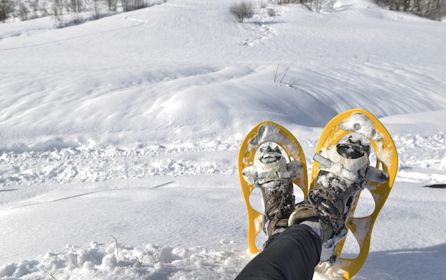 Foot of woman with snowshoes  in the snow