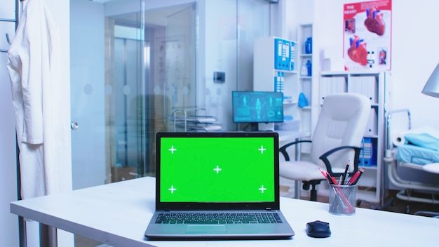 Footage of laptop with green screen display in hospital doctor wearing coat arriving in health clinic and nurse working on computer in cabinet. notebook with replaceable screen in medic clinic.