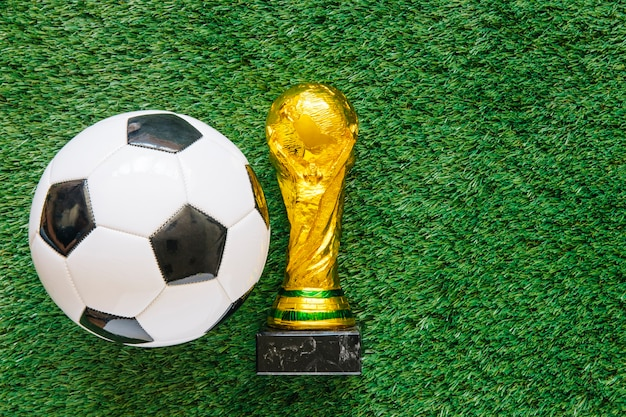 Sfondo di calcio su erba con palla e trofeo