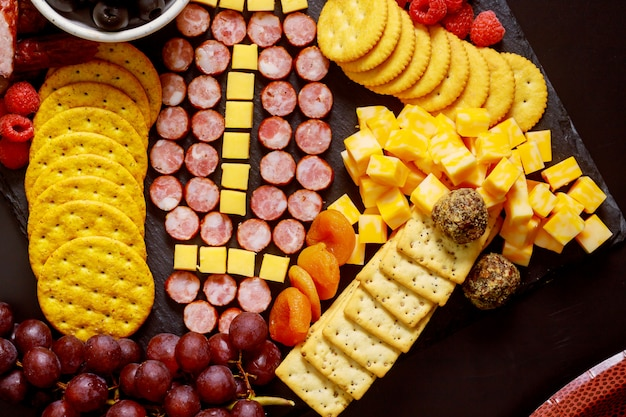 Football ball made from cheese and sausage for charcuterie board. american football game concept.