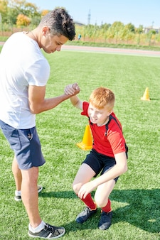 Football  coach helping boy